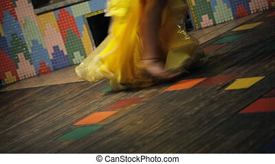Legs dancer in a yellow skirt and sandals on a colorful circle floor.