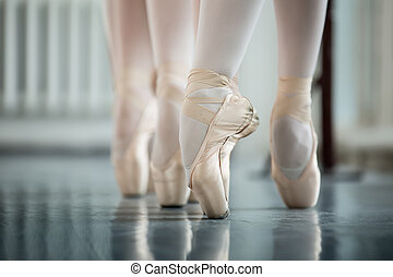 Legs dancers on white pointe, near the choreographic training ma