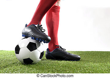legs feet football player in red socks and black shoes posing with the ball playing on green grass pitch