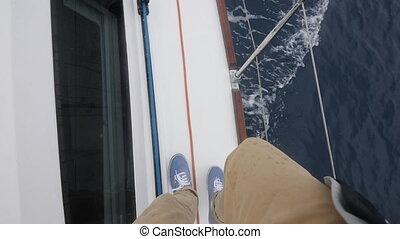 Legs feet of man walking along deck of white luxury yacht...