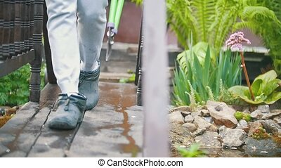 Legs gardener goes with clippers in his hands on the bridge,...