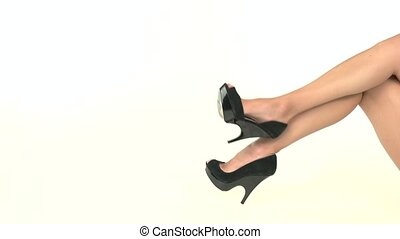 Dark footwear on heel. - Legs in black heels. Dark footwear...