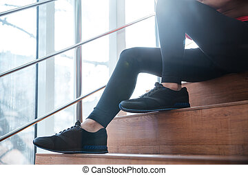 Legs in black leggings of young sportswoman sitting on ...