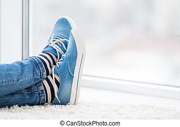 Legs in striped socks and blue gumshoes indoors