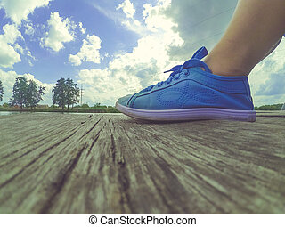 Legs in blue moccasins on a wooden dock