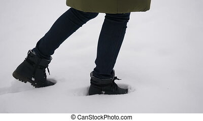 Legs in boots walks through thick white snow. Close-up shot...
