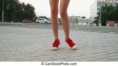 Legs in red sneakers steps on pavement closeup