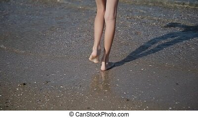 Legs in sea water, with an influx of waves. - Legs in sea...