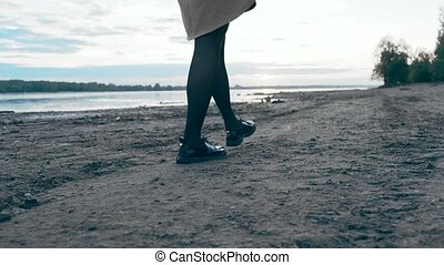 Legs in shoes. A young girl walks the riverbank. The camera ...