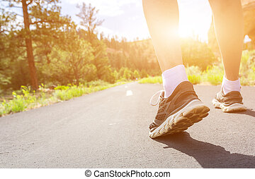 Legs in sport shoes on road at sunset closeup.