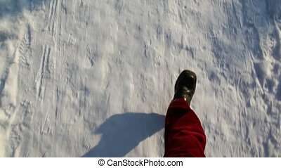 Legs in the red pants and black boots walking on snow