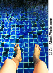 Legs in the swimming pool with blue tiles