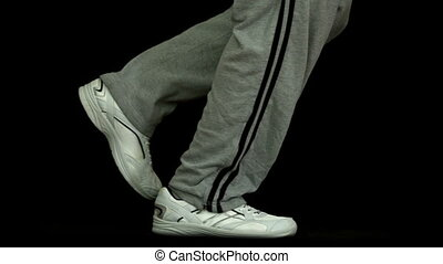 Legs in tracksuit running against black background in slow...
