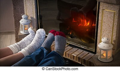 Legs in woolen socks heat up near fireplace