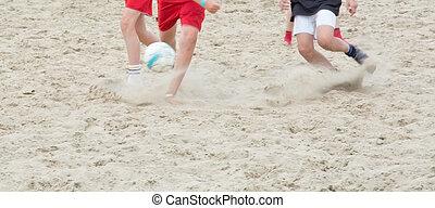 Legs kicking ball in sand