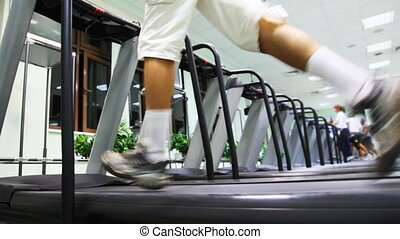legs man quickly run on one of many treadmill in large gym