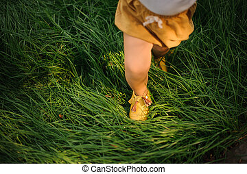 Legs of a baby girl in yellow shoes on green grass.
