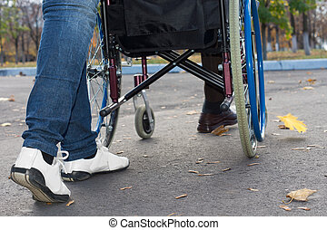 Legs of a carer pushing a wheelchair
