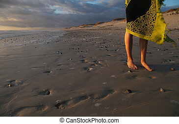 Legs of a girl at sunset on the beach of the Atlantic coast