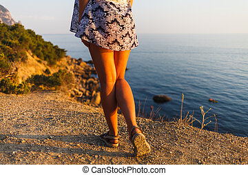 Legs of a girl in a dress on the beach