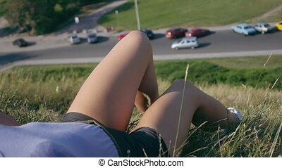 legs of a girl lying on the grass on a hill near the road