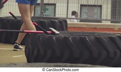 Legs of a man hitting tire with a hammer