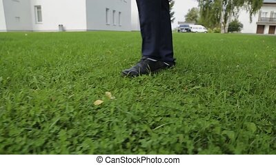 Legs of a man in trousers walking on the grass.