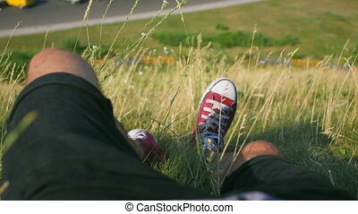 legs of a man lying on the grass on a hill near the road