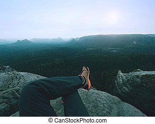 Legs of a man on rock. Hiker resting in boots for mountain
