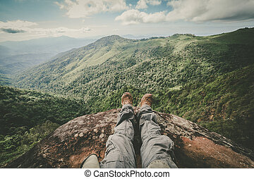 Legs of a man sitting on the edge