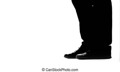 Legs of a man's girl get on toes. Silhouette. White...
