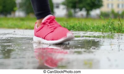 Legs of a runner in sneakers. Sports woman jogging outdoors,...