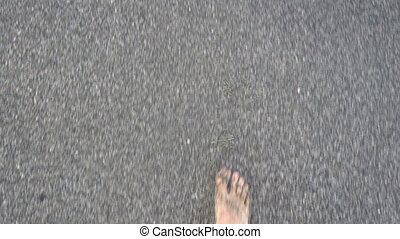 Legs of a tanned Caucasian man walking barefoot on a sandy...