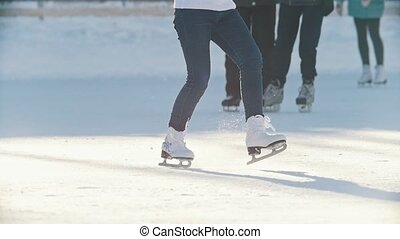 Legs of a teen girl skillfully skating on outdoor public ice...