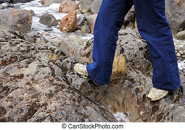 Legs of a woman hiker walks over rocks