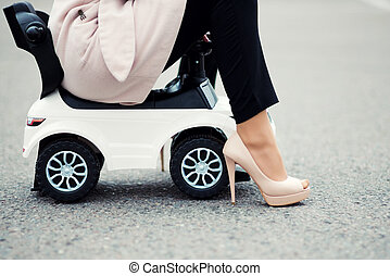 legs of a woman sitting on a baby car that is standing on the parking, toned