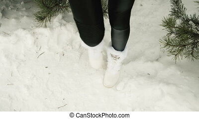 Legs of a woman trying to keep warm under spruce in frosty weather.