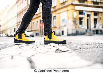 Legs of a woman walking on the street in town.