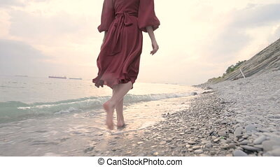 Legs of a young girl with a red dress from behind walking on a rocky beach the sea coast at sunset. A dress fluttering in the wind in the wind.