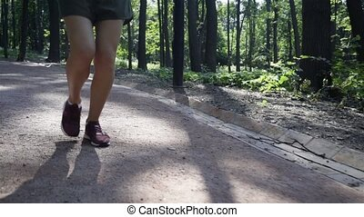 Legs of an unrecognizable young woman jogging in a park