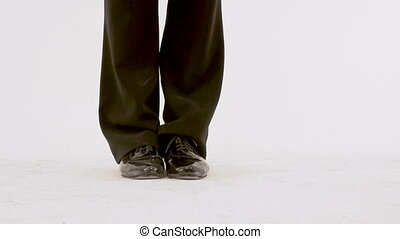 Legs of ballet men close-up, dancer in black suit performs retro dance on white background. He moves beautifully and flexibly, expressive speech.