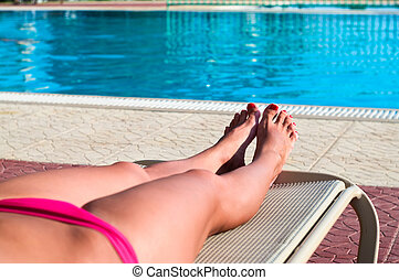 Legs of beautiful young unrecognizable girl in a bikini lying on a beach bed near the hotel swimming pool