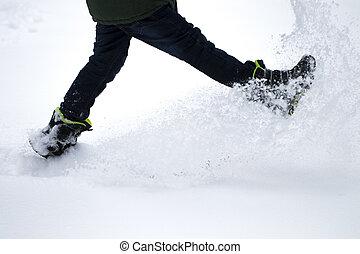 Legs of boy walks through the snow. Snow flies from under his feet