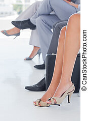 Legs of business people in line in a waiting room
