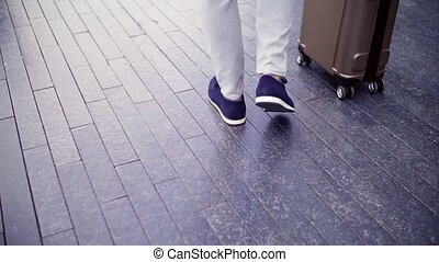 Legs of businessman with suitcase walking on a pavement. -...