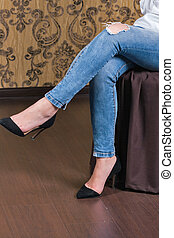 Legs of Caucasian woman sitting wearing torn jeans.