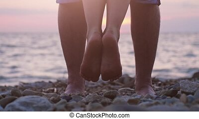 Legs of couple in love during the date by the sea on the beach during beautiful sunset. Man raising up on hand her loving woman in slow motion. 3840x2160