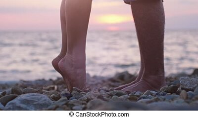 Legs of couple in love during the date near the sea on the beach during beautiful sunset. Man raising up on hand her loving woman and girl gets up on her toes reaches out to her man. 3840x2160