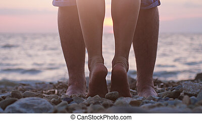 Legs of couple in love near the sea on the beach during beautiful sunset.