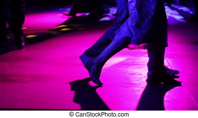 Legs of couple learning to dance tango and honing skills in...